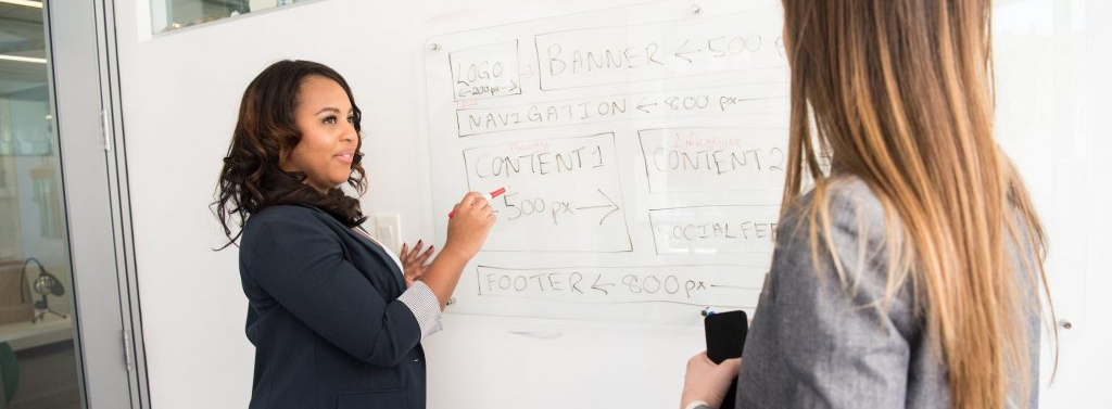 A mentor teaching in front of a whiteboard