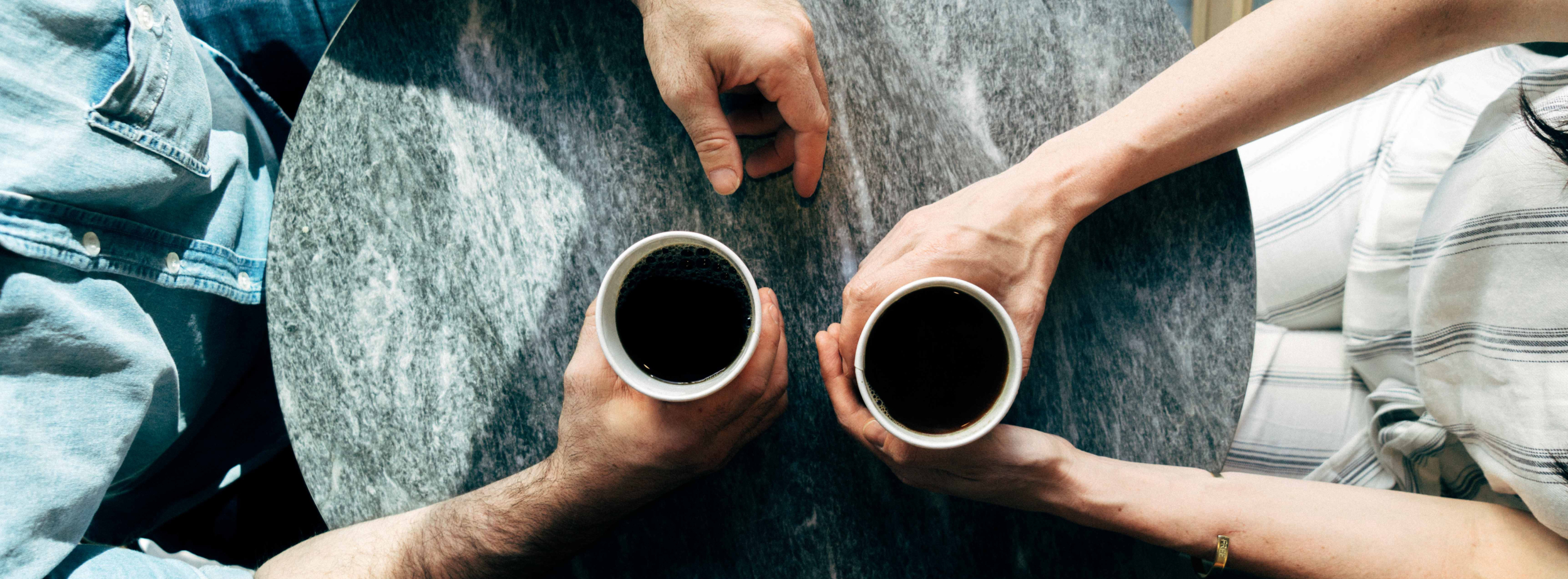 Two men with cups of coffee having a mock professional diiscussion